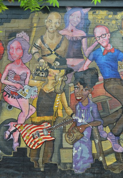 detail on mural - man in cowboy hat with a red & white striped guitar, amongst other people