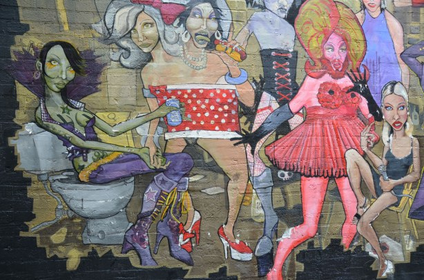 detail from mural - a bearded man in a pink dress, a woman in purple and two people sharing the same red & white polka dot dress