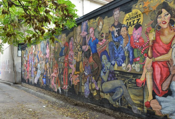 A picture of most of the mural.  There are many colourful characters on a wall that is about 8 feet long.  The mural is close to 20 feet long.