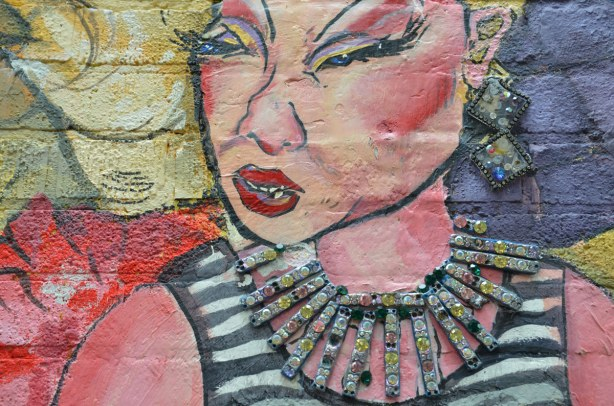 detail from mural - close up of woman with black and white striped top, glittering neacklace and ear rings