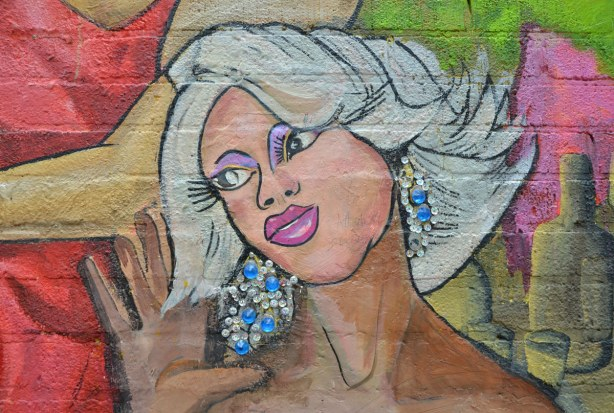 detail from mural - close up of woman with white hair and long eye lashes.  She is wearing blue and silver sparkly er rings