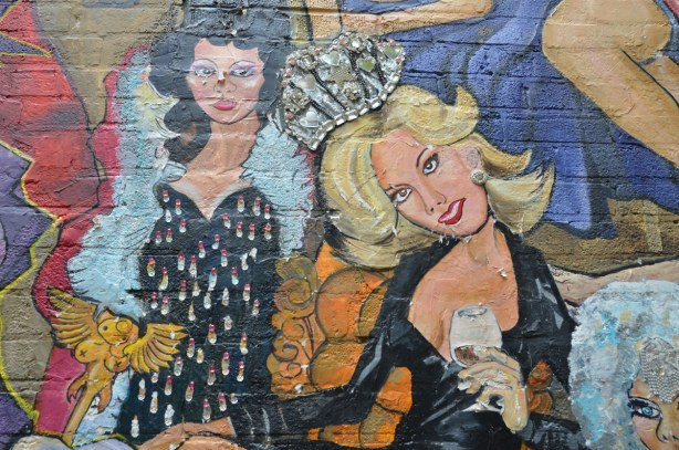 detail of mural - two women, one in black low cut dress and silver sparkly crown and the other in a bejeweled black dress and white fur boa.