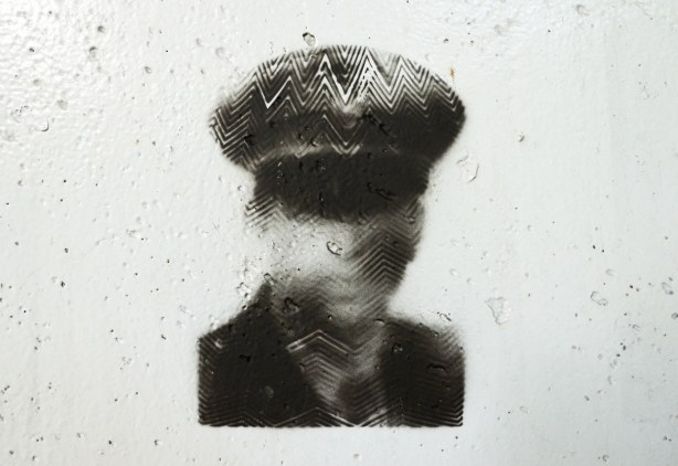graffiti under a bridge - black and white picture of a man in jacket and tie and a hat with a brim.  The top part of his face is in shadow from the hat brim.  He iis shown only from the shoulders up