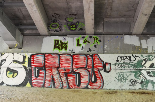 graffiti under a bridge - Crisis?  Cress? In large red letters with green and black drawings above (under the beams that are supporting the bridge)