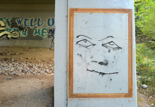 graffiti under a bridge - yellowish gold frame with large line drawing of a smiling person.