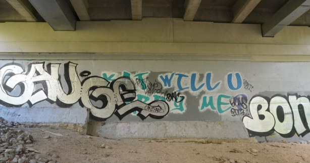 graffiti under a bridge - Kat Will you Marry Me?  was the original words on the wall.  It is partially obscured by a tag.