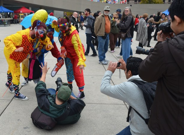 Three clown zombies are posed over a man who is lying on his back on the ground and holding a camera.  There is a small crowd around them, many with cameras.