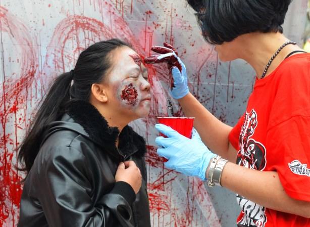 a zombie with a large gash in her face is having fake blood applied to her face by a zombie enabler