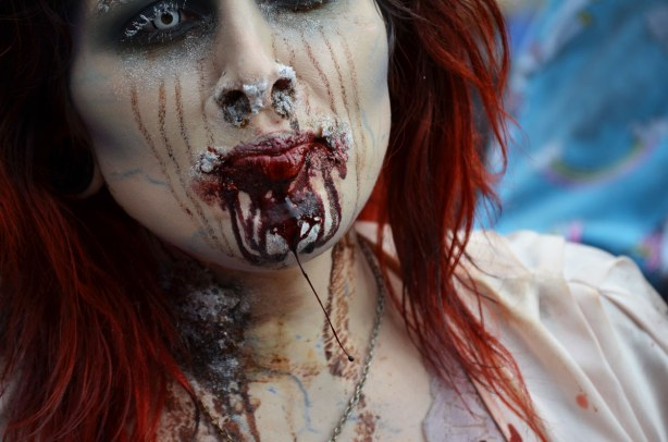 zombie woman with scratch marks on face and blood dripping down her chin.  Close up of just her head and shoulders.  Long red hair.