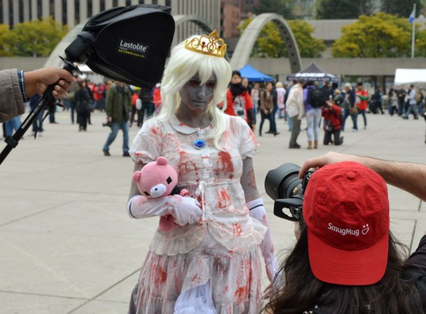 A hite haired, grey faced zombie holding a pink stuffed animal, and wearing a gold crown is posing for pictures for a guy with a large camera.  Another man is holding a light source beside the zombie