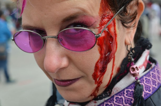 zombie from Toronto zombie walk, woman with pink sunglasses and skull earrings