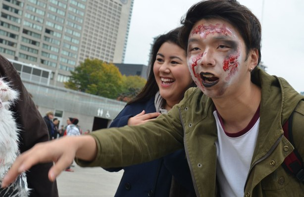 zombie from Toronto zombie walk, woman giggling as she poses beside a young man with his face made up to look like a zombie