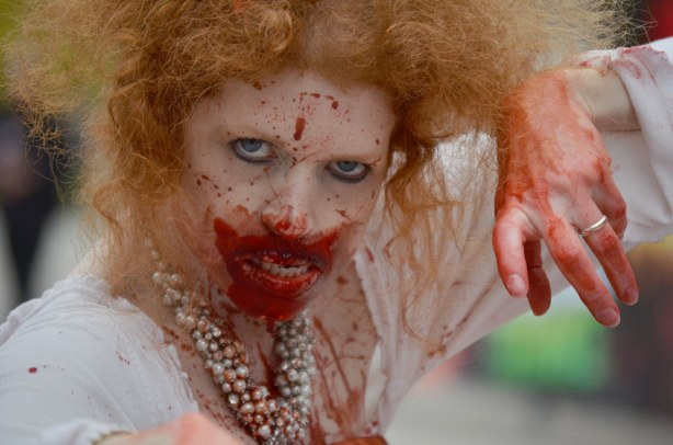 pale zombie with curly lught auburn hair, bloody chin and white dress.  She is glaring at the camera with her hand poised to reach for it.
