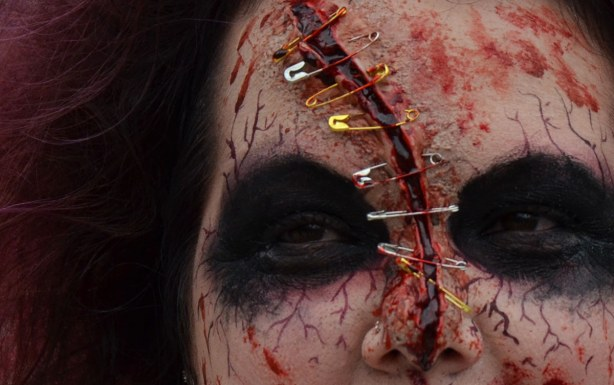 close up of zombie nose, eyes and forehead.  Eight safety pins are keeping her forehead together.
