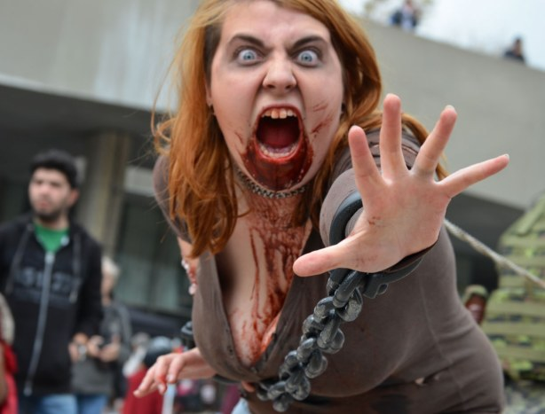 screaming woman zombie lunging for the camera but she is restrained by chains