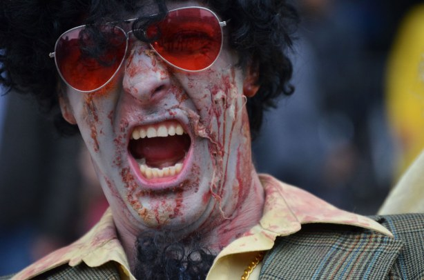 close up of a male zombie with reddish sunglasses.  He is screaming with his mouth wide open.