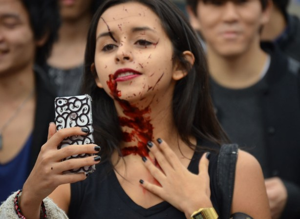 a girl is taking a selfie of herself after she has had a handprint of fake blood put on her neck