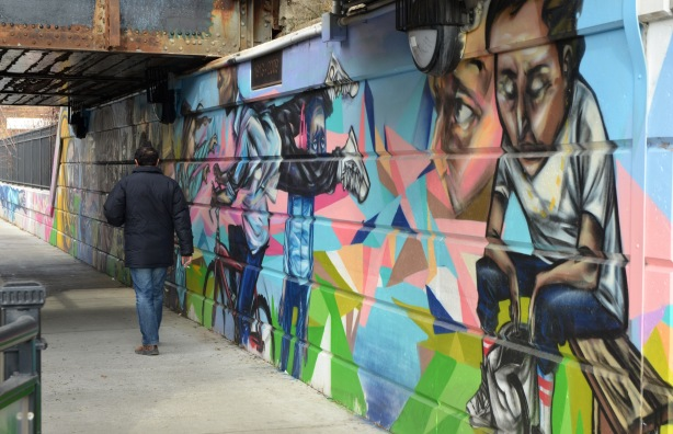 A man in a blue winter coat is walking under a bridge, beside a mural that is painted on the wall of the bridge.