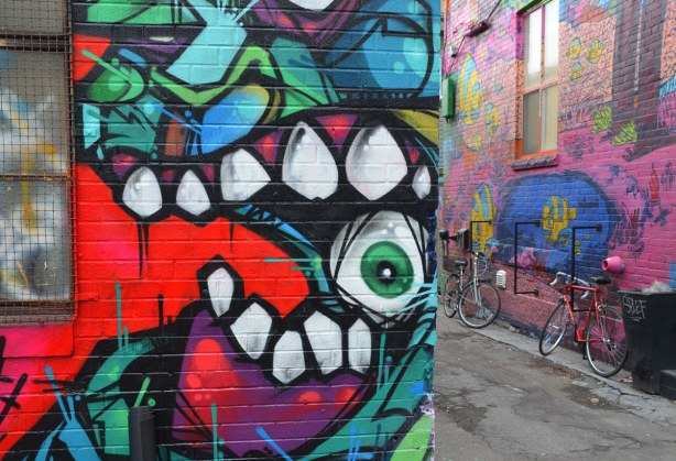Street art in Graffiti Alley, detail showing what looks like an eye between two sets of teeth.  In the background, and to the right, are two bikes parked against the building that is covered with uber 5000's marine scene