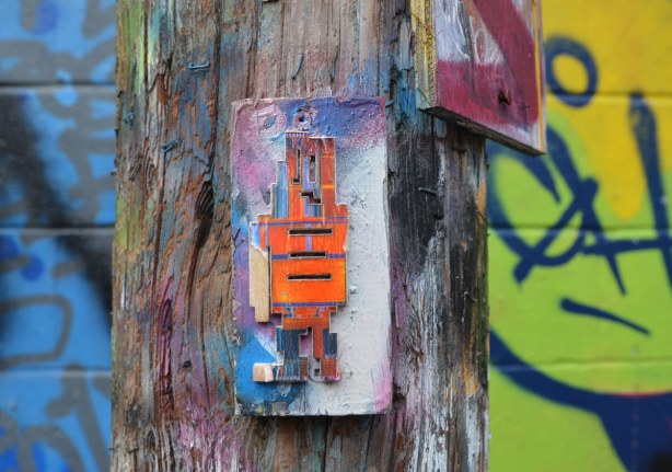 Street art in Graffiti Alley, an orange stickman (stickman?) on a hydro pole.