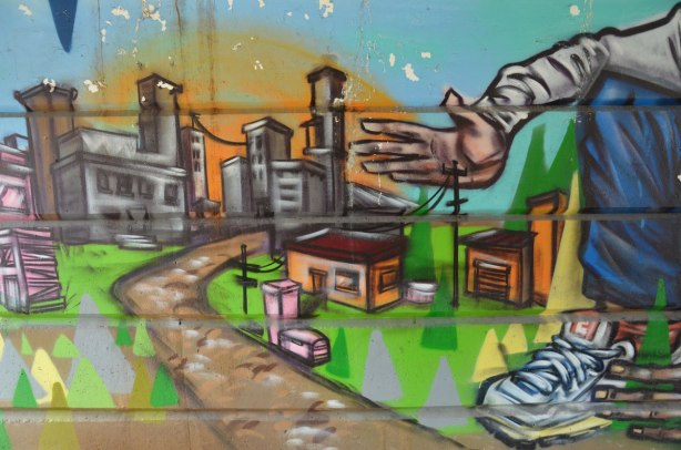 part of a mural beside the walkway under a railway bridge - a man's hand reaching towards a miniature city.  roads, houses, tall buildings and hydro wires