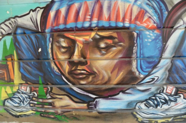 part of a mural beside the walkway under a railway bridge - a man with a football helmet on and green triangles in his hand