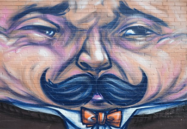 close up of mural, showing man's face with furrowed brow and black moustache.