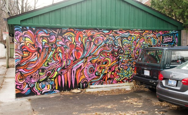 street art mural on the side of a garage door, multicoloured shapes and lines with the words 'escape reality' written in the top right corner