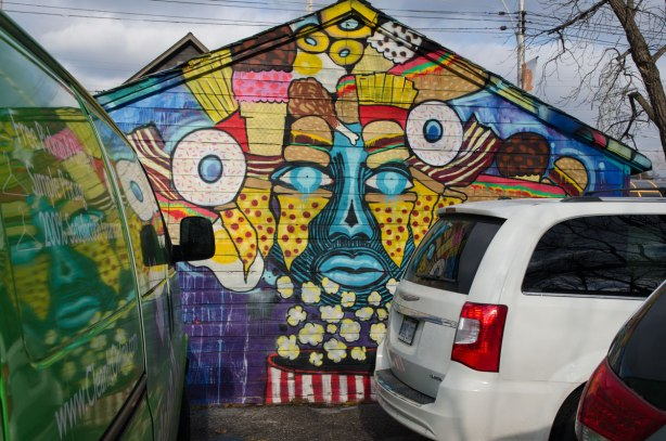 A van and car parked in front of a street art mural of a face in blue, yellow and red that is surrounded with stylized food, especially candy and popcorn.  The neck is an iconic red and white striped popcorn container.  The picture is reflected in the windows of the van.