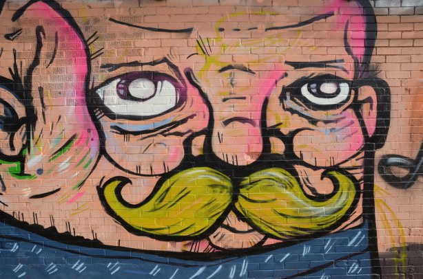 close up of mural, showing man's face including white eyes and a green moustache.