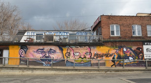 looking across the street to a mural to commemorate Movember.  Two large men's faces, both sporting moustaches beside the word Movember written in cursive.