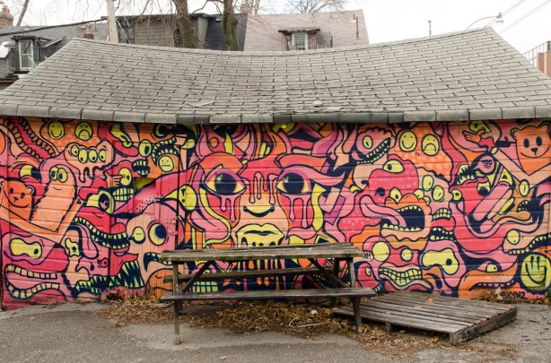 A wood picnic table is in front of a street art mural on the side of a garage door
