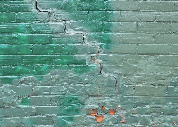 A brick wall painted in two shades of shiney green paint.  There is a large crack running diagonally across the wall.