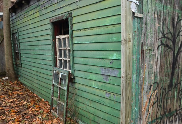 A green garage in need of paint.  A window frame is sitting on the ground beneath the window.  Dead leaves on the ground.