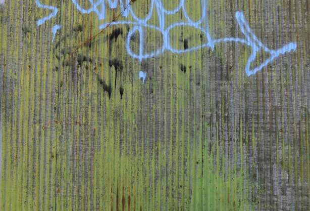 streaks of greenish discoloration as well as rust on the side of a corrugated metal wall