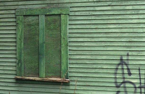An old boarded up window on a wood wall, all painted green
