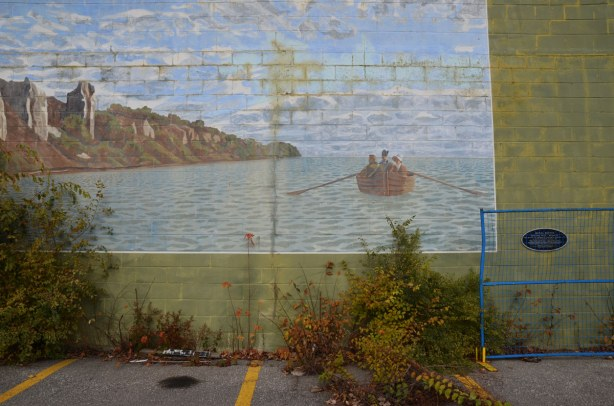 mural on the side of building depicting an early scene from Canadian history - a small rowboat with a couple of people in it is passing by the cliffs that are now known as the Scarborough bluffs.