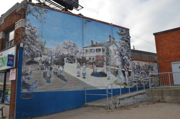 A mural that takes up the side of a building.  It is a picture of an old two storey inn.  It is a street scene as well, with people wearing clothes from the late 1800s.