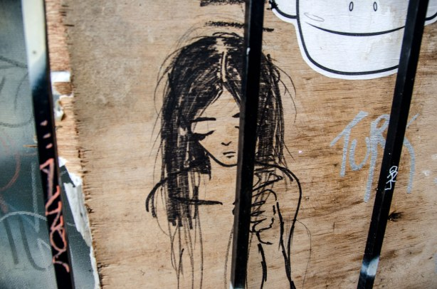 A girl with long dark hair and with her eyes closed.  From the shoulders up with one arm and hand included in the picture. Drawn on plywood and behind bars.