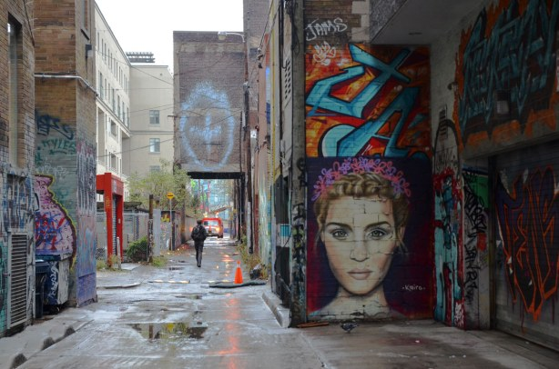 looking down the alley, graffiti on the walls on both sides including a large woman's head by the artist Kairo.  She has curly hair and her face is about 7 feet tall.