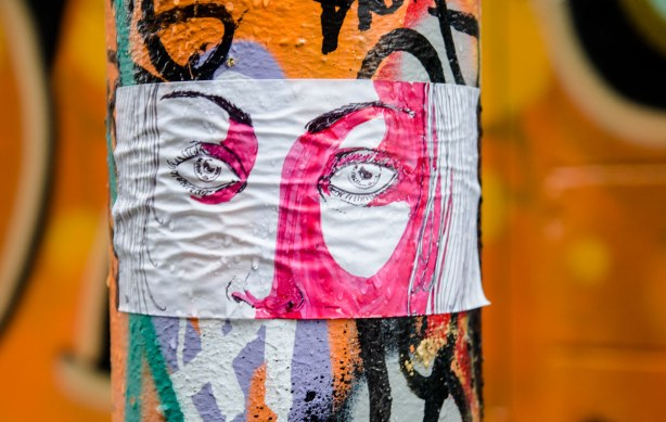 sticker of eyes on a white and pink face.  The sticker is on a pole and there is an orange wall that is out of focus  behind the pole.