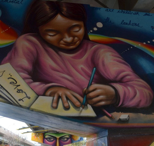 Paintings on the large T shaped concrete supports of the overpass, a young girl in a pink top sitting at a table and writing in a notebook.  The word love is written on one of the pages.