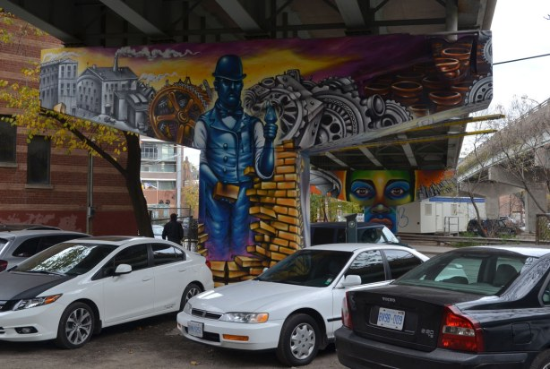 Mural on concrete pillar of a blue brick layer surrounded by symbols of industry such as factories, gears, beer bottles, bricks.  There is a parking lot surrounding the concrete support so there are cars parked in front of the pillar.