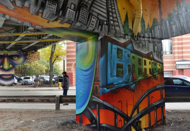 Paintings on the large T shaped concrete supports of the overpass,  a man passes by on the sidewalk while in the foreground is a support painted with street scenes.  Houses and streetcar tracks.