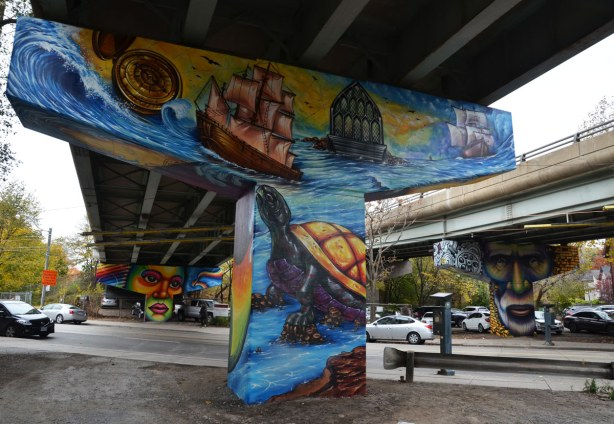 Paintings on the large T shaped concrete supports of the overpass, three supports are in the picture.  The one in the foreground has marine scenes - two sailing ships, a large turtle, and waves.  The two supports in the background are those with faces, one man and one woman.