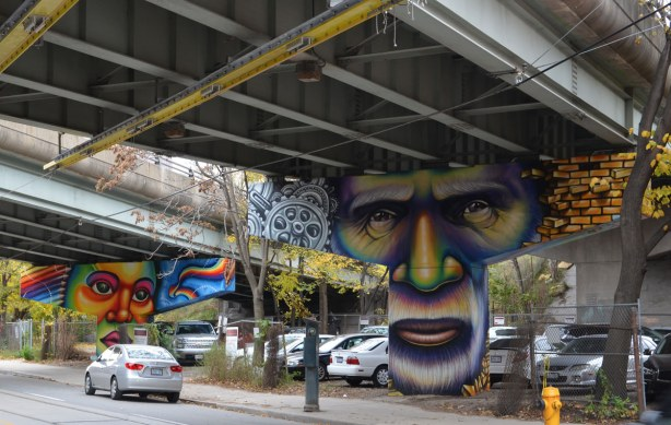 Paintings on the large T shaped concrete supports of the overpass, in  the foreground is the face of a man with the eyes on the upper horizontal portion of the support and his mouth on the lower part.