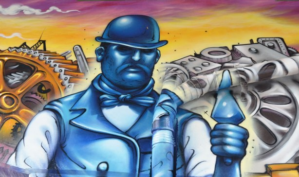 Paintings on the large T shaped concrete supports of the overpass, a man portrayed in blue tones, wearing an old fashioned hard hat and holding a trowel.