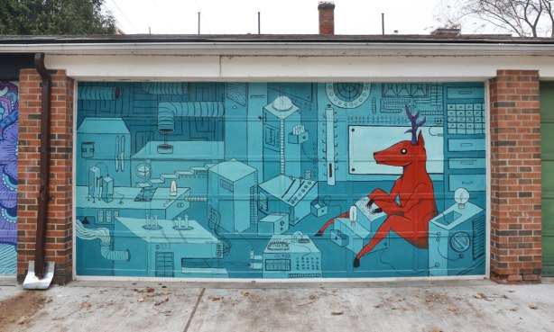 street art mural on an alley garage door.  A red deer is seated in what looks like a computer lab, or factory.