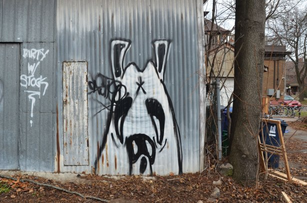 graffiti of a black and white dog's face on a metal garage