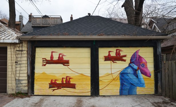 street art mural on a double garage.  yellow background.  three floating logs with birds sitting on them are being pulled by a creature with a pink and purple head as well as a blue body.